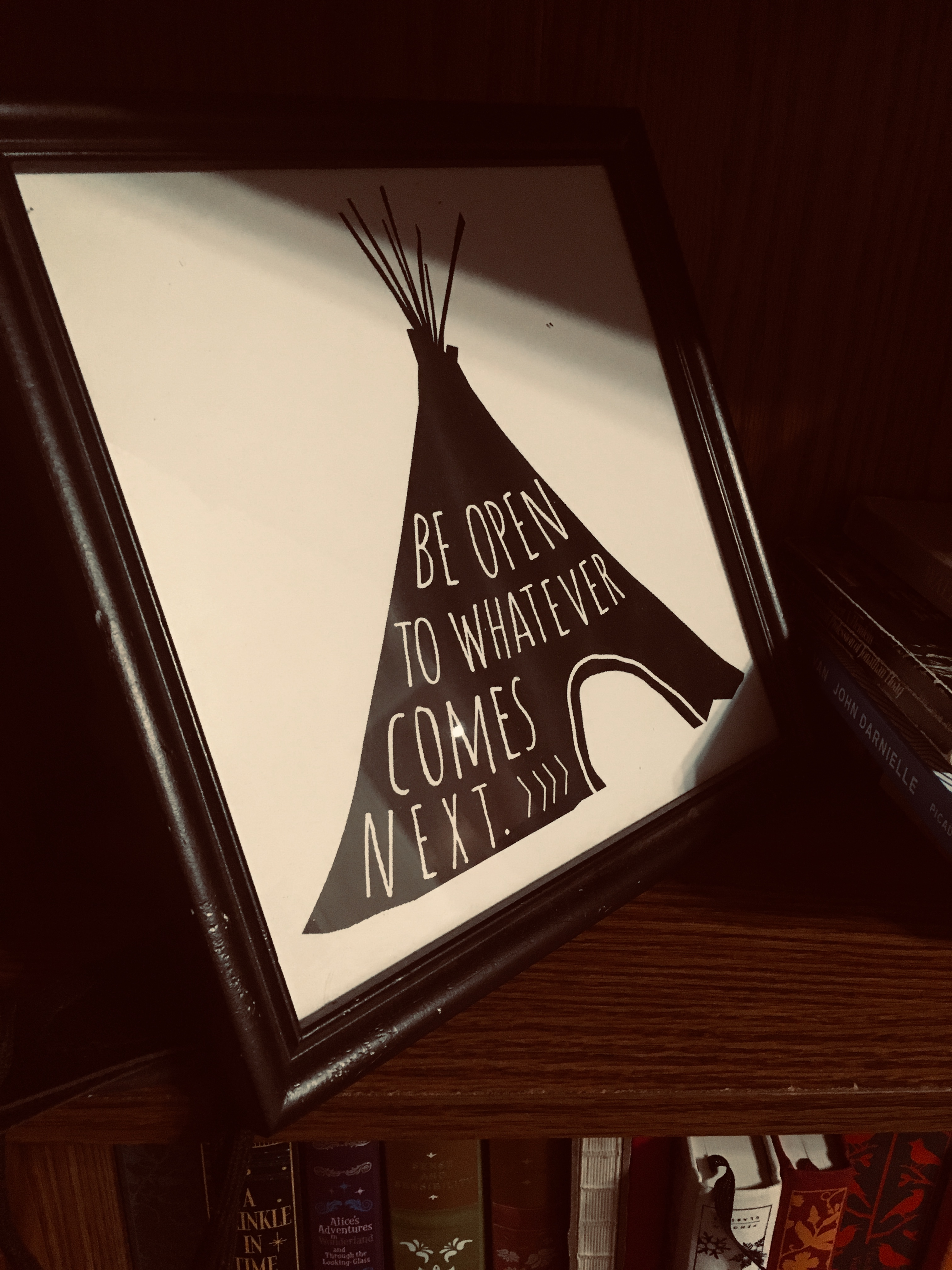 """A framed photo of a print featuring a drawing of a tepee with the words """"Be open to whatever comes next"""" on it."""